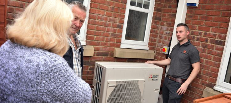 A Marshall & McCourt heat pump engineer showing customers how to use their new air source heat pump