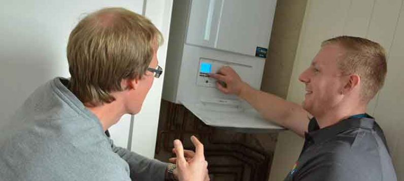 A Marshall & McCourt gas engineer showing a client how to use his new boiler
